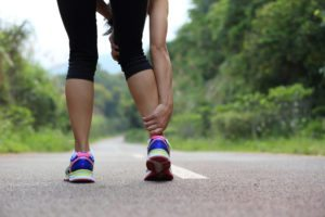 Female runner holding her ankle